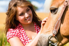 Woman petting horse - pony farm Stock Images