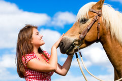 Woman petting horse on pony farm. Young Woman petting horse on pony farm Royalty Free Stock Photos
