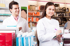Woman pharmacist at the chemists shop. Smiling harmacists men and harmacist women writes in a notebookat the chemists shop of a white coat royalty free stock images
