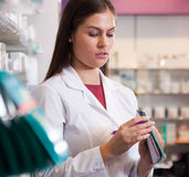 Woman pharmacist at the chemists shop. Young woman in a white robe with a notebook in hand at the pharmacy stock photo