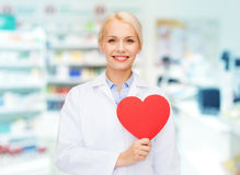 Woman pharmacist with heart at drugstore. Medicine, pharmacy, people, health care and pharmacology concept - happy young woman pharmacist holding red heart shape stock images