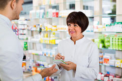 Woman pharmacist helping customers in drug store Stock Photo