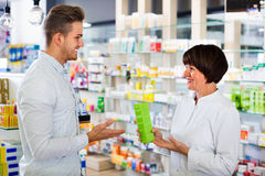 Woman pharmacist helping customers in drug store Royalty Free Stock Image