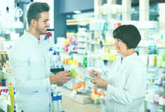 Woman pharmacist helping customers in drug store Royalty Free Stock Images