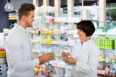 Woman pharmacist helping customers in drug store Stock Image