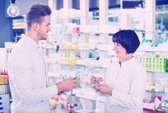 Woman pharmacist helping customers in drug store Stock Photos