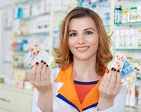 Woman pharmacist presenting medicine Stock Images