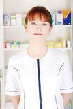 Woman in pharmacist uniform in drugstore Royalty Free Stock Photos