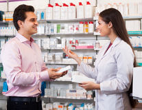 Woman pharmacist and visitor at the chemists shop Royalty Free Stock Photography