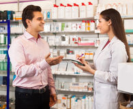 Woman pharmacist and visitor at the chemists shop. Pharmacist women offers the visitor a cure at the chemists shop stock photography