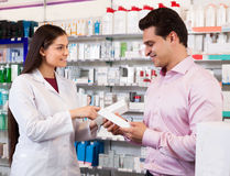 Woman pharmacist and visitor at the chemists shop Royalty Free Stock Photo