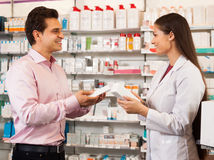 Woman pharmacist and visitor at the chemists shop royalty free stock image