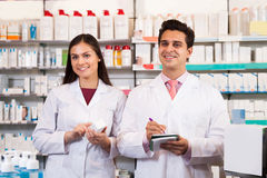 Woman and pharmacists at the chemists shop. Smiling women and men pharmacists in white coats at the pharmacy royalty free stock image