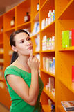 Woman in pharmacy thinking Royalty Free Stock Photo