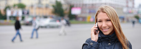 Woman with phone. Happy young woman speaks by phone on the street Stock Photos