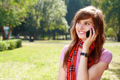 Woman with phone. Happy young woman speaks by phone outdoors Royalty Free Stock Photo