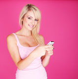 Woman with phone. Portrait of young blonde woman sending a text on pink background copyspace stock photo