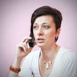 Woman on Phone. Beautiful business woman on the phone over pink background Royalty Free Stock Photo