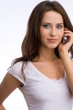 Woman on the phone. Portrait of a beautiful young woman wearing a white shirt talking on the phone Royalty Free Stock Images