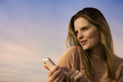 Happy young woman with mobile. Side portrait of happy young woman using mobile telephone with sky and cloudscape background at sunset Stock Photo