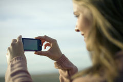 Woman taking picture with mobile Stock Photography