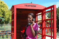 Woman on phone. A beautiful attractive young African American black woman with happy smiling expression in her face standing in a telephone box holding a phone Stock Image
