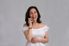Woman on phone. A beautiful latina lady dressed in white laughing on a cell phone, isolated on gray Royalty Free Stock Photos