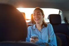 Woman with phone on the back seat of a car stock photos