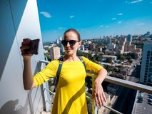 Woman with phone and backpack in the city 01. Pretty smiling woman makes selfie portrait on smartphone stock images