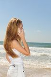Woman with phone on the beach. Woman talking on phone on the beach royalty free stock photos