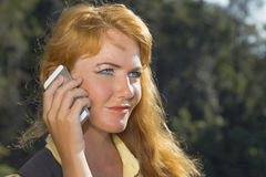 Woman with the phone. Beautiful red-haired girl talking on the phone in the mountains stock photography