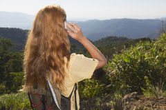 Woman with the phone. Beautiful red-haired girl talking on the phone in the mountains stock images