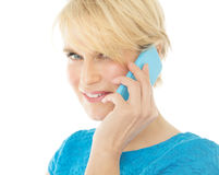 Woman On Phone. Beautiful smiling elegant woman indoors wearing blue blouse and talking on phone Stock Photos