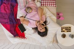 Woman with a phone in bed Stock Photo