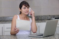 Woman on phone with bill Royalty Free Stock Images