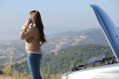 Woman on the phone beside a breakdown car. Woman on the phone asking for assistance beside her crashed breakdown car in a mountain road Royalty Free Stock Photography