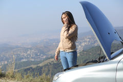 Woman on the phone beside a breakdown car. Woman on the phone asking for help beside her crash breakdown car in a road with a city in the background stock image