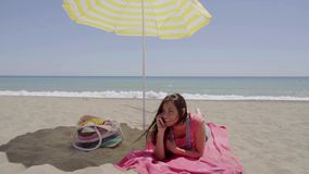 Woman on phone call at beach under umbrella. Woman on phone call at beach under yellow and white umbrella with ocean waves in background stock video footage
