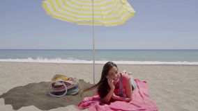 Woman on phone call at beach under umbrella. Woman on phone call at beach under yellow and white umbrella with ocean waves in background stock footage
