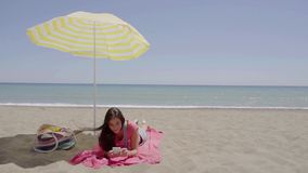 Woman on phone call at beach under umbrella. Woman on phone call at beach under yellow and white umbrella with ocean waves in background stock video