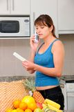 Woman on phone checking bill royalty free stock photo