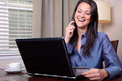 Woman on phone with credit card Stock Photography