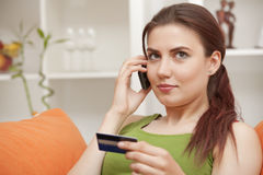 Woman on phone with credit card Royalty Free Stock Photography
