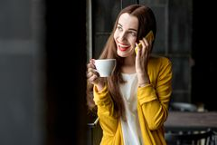 Woman with phone and a cup of coffee Stock Photos