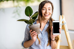 Woman with phone and flowerpot stock images