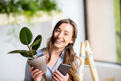 Woman with phone and flowerpot stock image