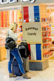 Woman on a phone in front of candy store with luggage in an airp Royalty Free Stock Image