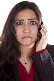Woman on phone frustrated up close. A woman is talking on her cell phone with a very frustrated expression on her face Royalty Free Stock Image