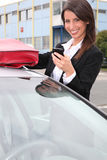 Woman with a phone by her car Royalty Free Stock Photography