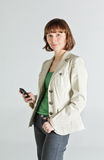 Woman with phone in her hand. Portrait of a middle aged woman holding smartphone Royalty Free Stock Photography